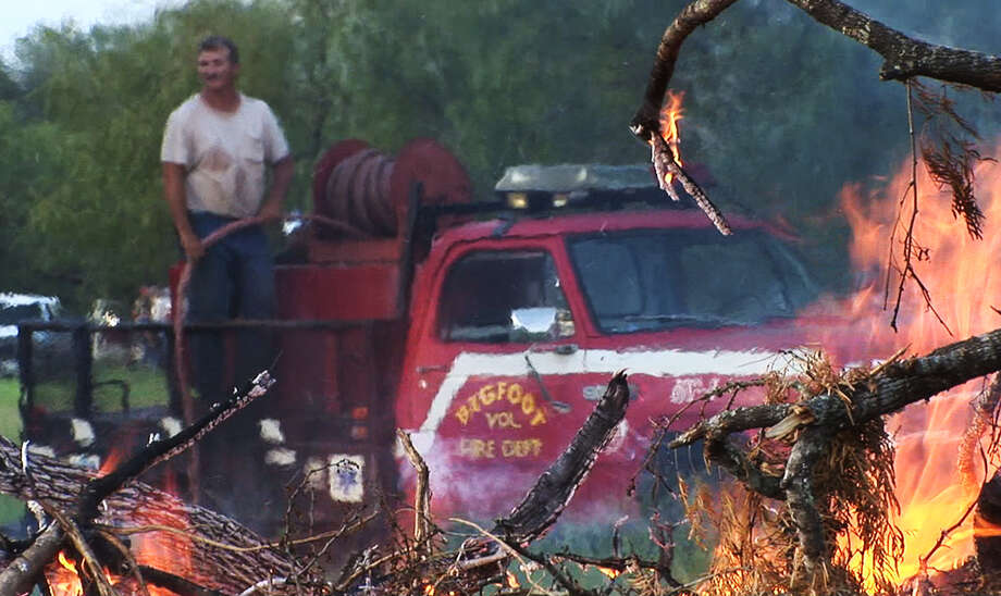 Heat waves from a brush fire blur the image of a volunteer with the Bigfoot Volunteer Fire Department as he stands on top of the department's newly donated brush fire truck during a controlled brush fire event in Frio County in 2008. The National Weather Service has issued a fire watch from 1 p.m. to 6 p.m. Tuesday for a large area west and southwest of San Antonio, including Hondo and Pearsall. Photo: Express-News File Photo / SAN ANTONIO EXPRESS-NEWS
