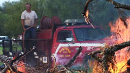 Heat waves from a brush fire blur the image of a volunteer with the Bigfoot Volunteer Fire Department as he stands on top of the department's newly donated brush fire truck during a controlled brush fire event in Frio County in 2008. The National Weather Service has issued a fire watch from 1 p.m. to 6 p.m. Tuesday for a large area west and southwest of San Antonio, including Hondo and Pearsall.