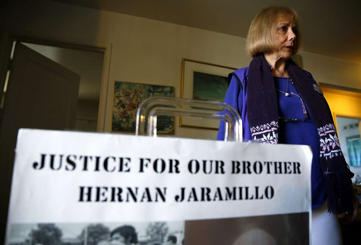 Ana Biocini stands beside a sign demanding justice for her brother that she carries at protests at her home in Oakland, California, on Sunday, Jan. 31, 2016.