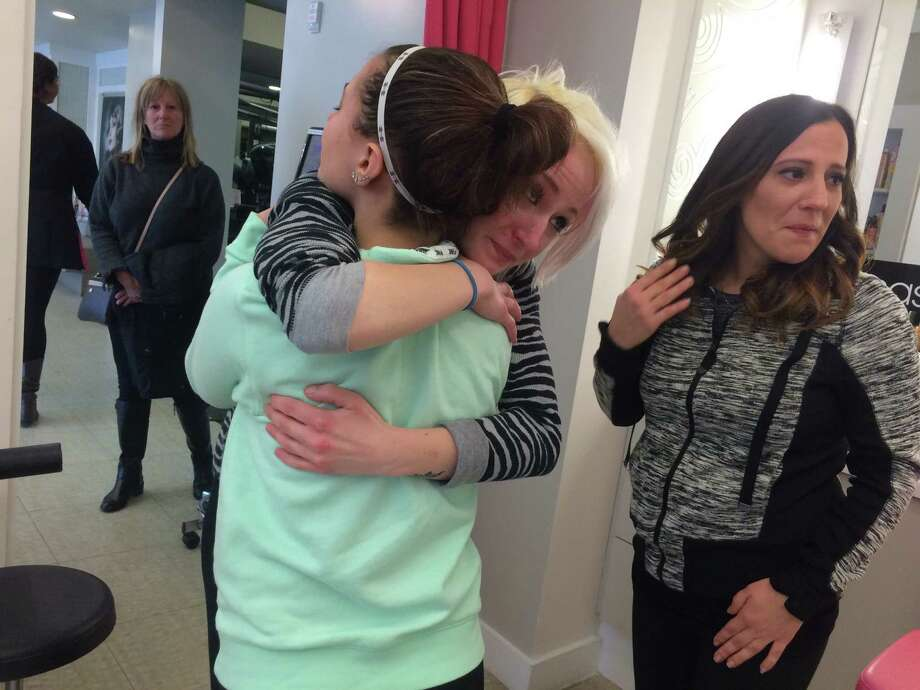 A staff member at Rumors Salon and Spa hugs Nevaeh Davis, 14. Davis and her mother, Venessa Cunsolo, right, narrowly escaped a Sunday morning fire at the Regency Park Apartments in Guilderland. (Cathleen F. Crowley/Times Union) Feb. 1, 2016