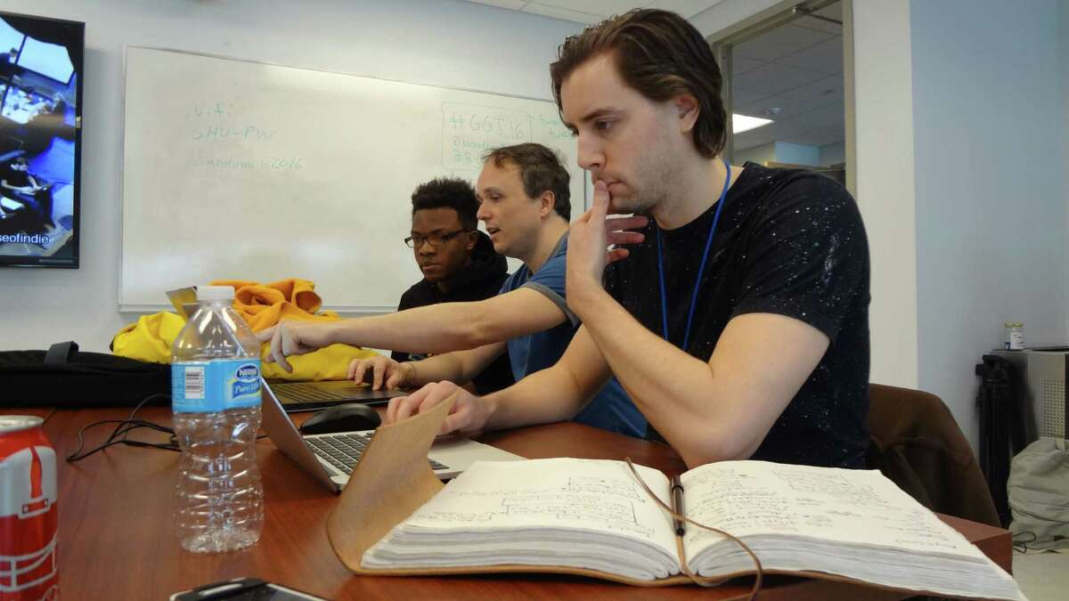"""Chris Stevens, Tao Langston and Erick Jean Pierre (R-L) create their game """"Alchymikal: Legacy of the Archon"""" on January 30, 2016, as part of the Fairfield County Game Jam @ SHU at Sacred Heart University's campus in Stamford, Conn., a participant site in the 2016 Global Game Jam held January 29-31, 2016."""