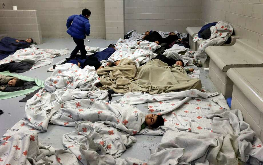 2014 YEAR IN REVIEW - FOR USE AS DESIRED --  Seen during a media tour, children sleep on the floor of a U.S. Customs and Border Protection center for unaccompanied minors entering the country illegally, in Brownsville, Texas, June 18, 2014. The unprecedented number of children arriving -- many fleeing gang violence in their native countries -- has presented the Obama administration with a humanitarian predicament as well as a political one. (Eric Gay/Pool via The New York Times) -- FOR EDITORIAL USE ONLY. ORG XMIT: NYT216 Photo: ERIC GAY / POOL