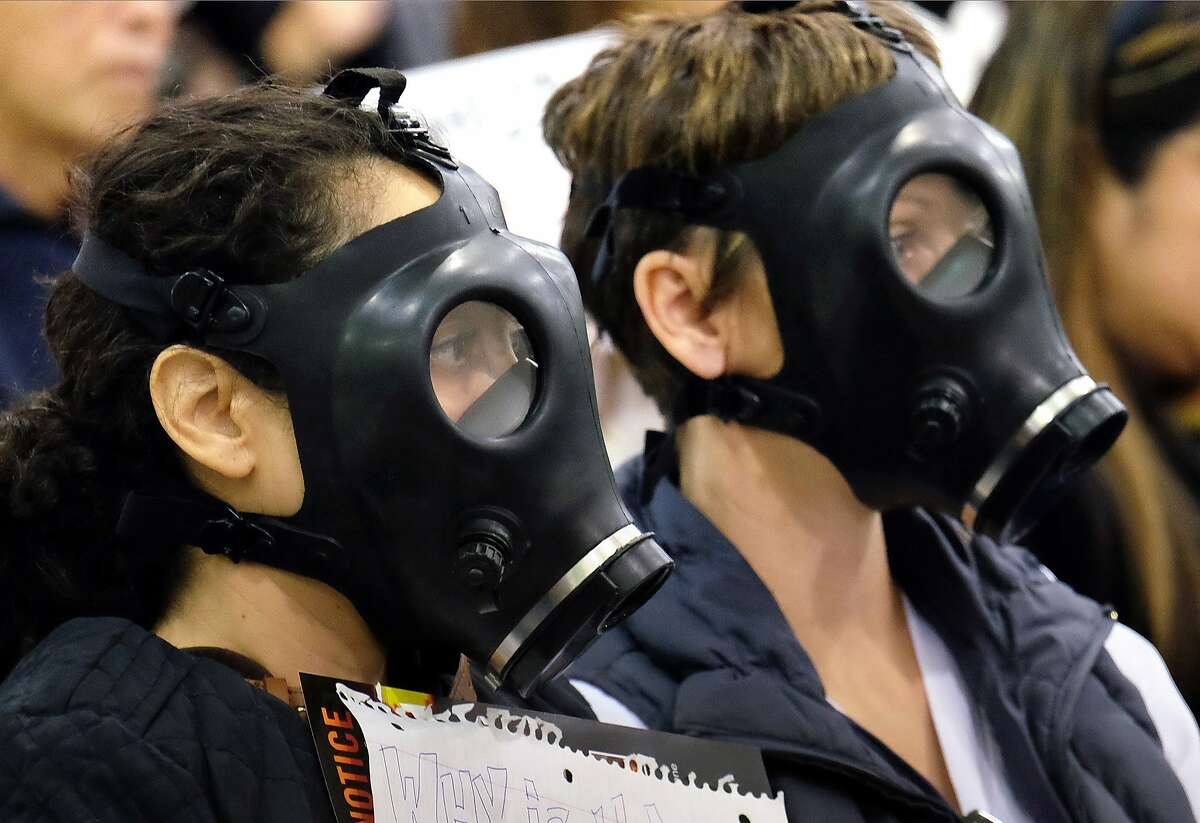 In this Jan. 16, 2016, file photo, protesters wearing gas masks attend a hearing over a gas leak at the southern California Gas Company's Aliso Canyon Storage Facility near the Porter Ranch section of Los Angeles.