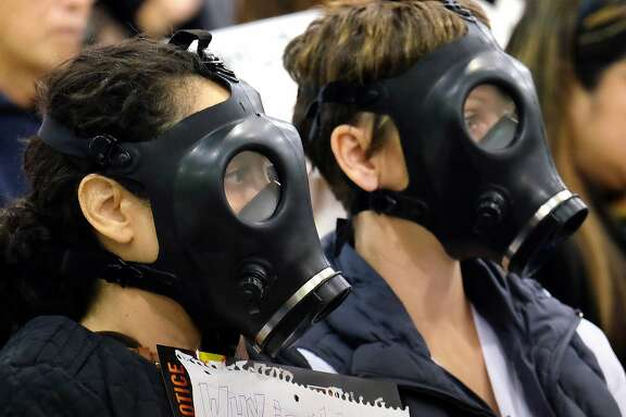 FILE - In this Jan. 16, 2016 file photo, protestors wearing gas masks attend a hearing over a gas leak at the southern California Gas Company's Aliso Canyon Storage Facility near the Porter Ranch section of Los Angeles.  The Southern California Gas Co. was told Saturday, Jan. 23, 2016, to permanently close and seal a storage well that's poured natural gas into the air over a Los Angeles neighborhood for months and driven thousands from their homes. (AP Photo/Richard Vogel, File)