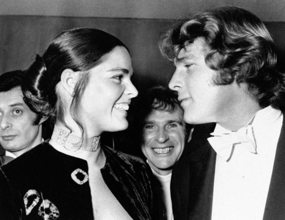 "FILE- In this March 8, 1971, file photo, Ryan O'Neal, right, and Ali MacGraw smile after their arrival at the Odeon Theatre, Leicester Square in London, to attend the Royal Film showing of ""Love Story."" Actors MacGraw and O'Neal are returning to Harvard University more than 45 years after the release of their 1970 classic ""Love Story."" The duo, now in their 70s, will be reflecting on their careers Monday, Feb. 1, 2016, in a conversation moderated by arts journalist Alicia Anstead. (AP Photo, File) ORG XMIT: NY107 / AP"
