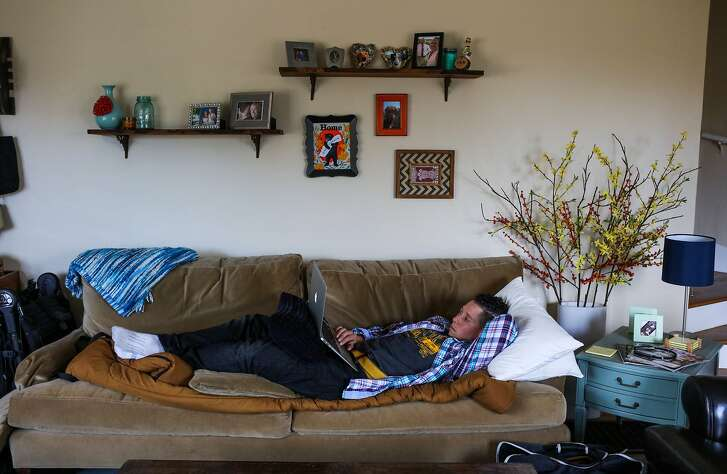 Allison Leshefsky, a Physical Education teacher, relaxes on the couch at her friend Sarah M.'s house, which is where she has been sleeping since being evicted from her apartment, in Oakland, California on Saturday, January 30, 2016.