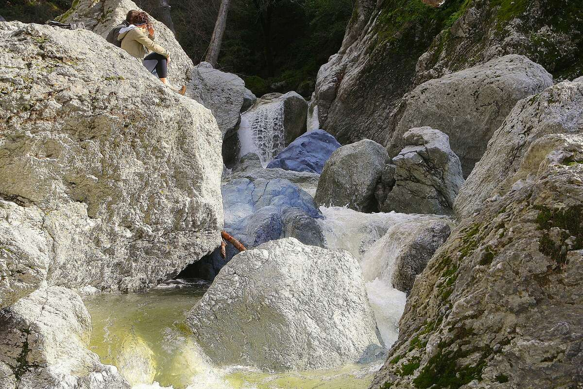 Faith Henry and Rafer Clive enjoy a rock perch amid a succession of miniature waterfalls in a pool-and-drop rocky gorge of Little Yosemite at Sunol-Ohlone Regional Wilderness in East Bay hills near Sunol