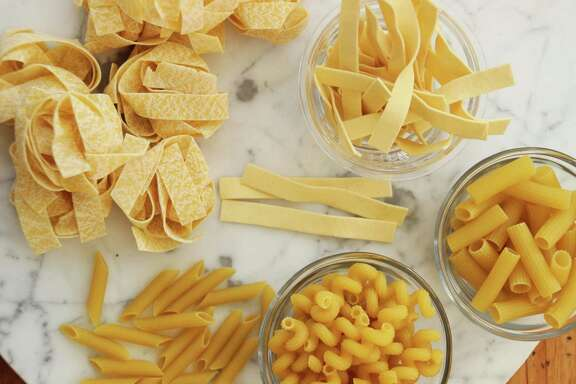 This Jan. 11, 2016 photo shows an array of dried pastas for making easy weeknight pasta dinners.  Clockwise from top, egg noodles, ziti, cavatappi , penne and pappardelle, in Concord, NH. (AP Photo/Matthew Mead)