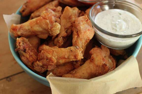 This Nov. 16, 2015 photo shows hands off party wings with cilantro sour cream dip and honey sriracha in Concord, N.H. These wings require almost no effort from you. The secret is baking powder. (AP Photo/Matthew Mead)