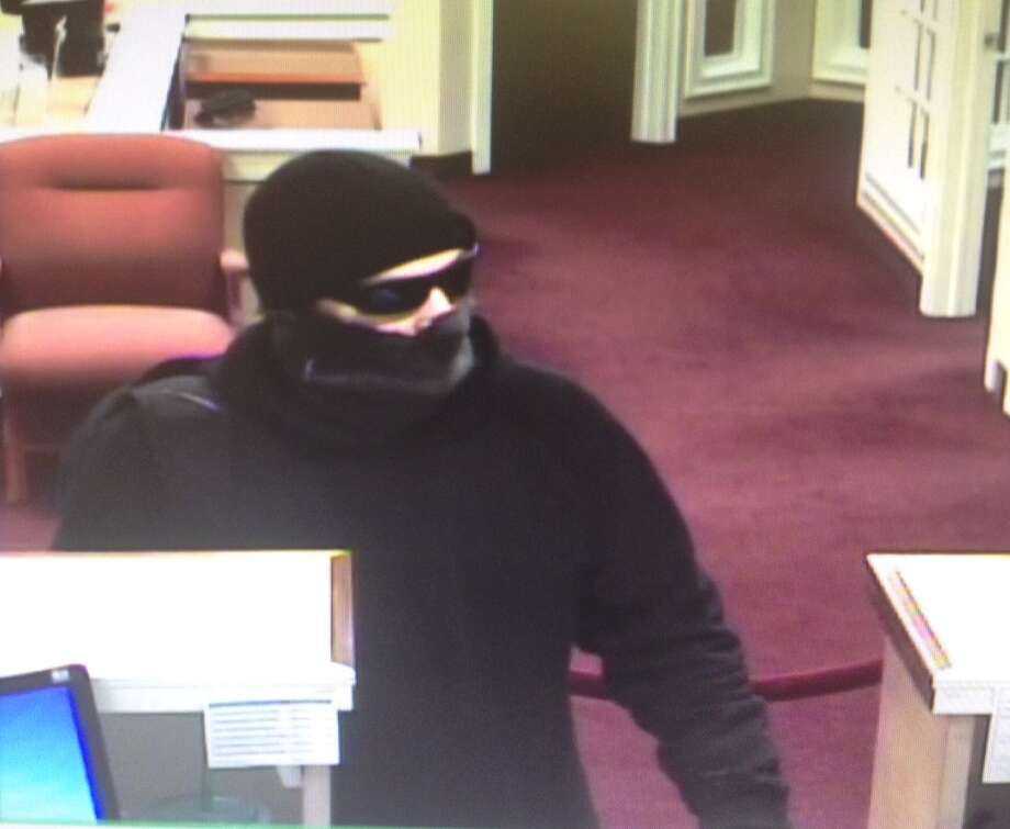 "Police said a lone white male, approximately 5'10"" tall wearing a black, pull-over style hooded sweatshirt, a black knit cap, black sunglasses and a pulled-up black neck gaiter entered the the Union Savings Bank in Brookfield carrying a black backpack and demanded money from the teller drawers."