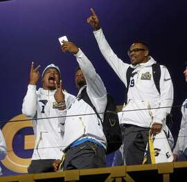 Carolina Panthers' Cam Newton and Jonathan Stewart take a selfie as Ted Ginn, Jr. acknowledges the cheers during Super Bowl 50 Opening Night at SAP Center in San Jose, Calif., on Monday, February 1, 2016.