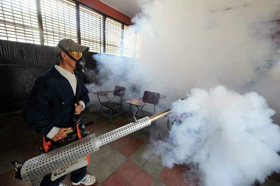 Health ministry personnel fumigate against the Aedes aegypti mosquito, vector of the dengue, Chikungunya and Zika viruses in Tegucigalpa, , on February 1, 2016. Honduran President Juan Orlando Hernandez on Friday declared the country on a preventive state of alert due to the Zika virus which in the last 44 days killed a person and infected some 1000.      AFP PHOTO/Orlando SIERRA.ORLANDO SIERRA/AFP/Getty Images ORG XMIT: 314 Photo: ORLANDO SIERRA / ORLANDO SIERRA
