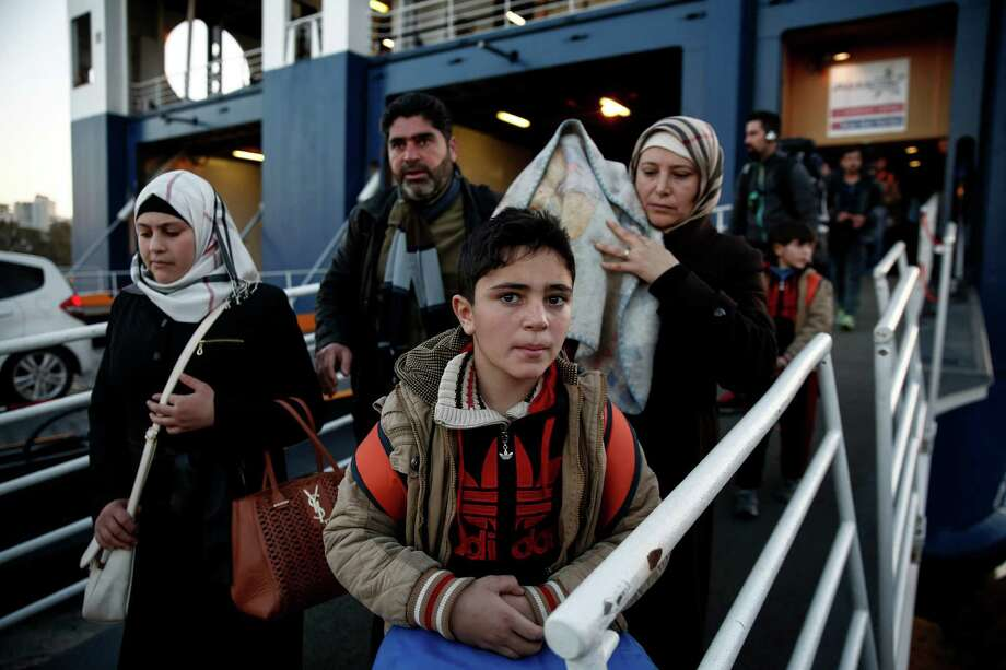 Migrants and refugees disembark from a ferry after their arrival at the port of Piraeus near Athens, Sunday, Jan. 31, 2016. Europe has endured a huge influx of migrants, most of whom undertake a dangerous journey in search of a better life. On Saturday, at least 37 people drowned, including children and babies, when their boat capsized during the short trip from Turkey to Greece. (AP Photo/Yorgos Karahalis) ORG XMIT: XYK113 Photo: Yorgos Karahalis / AP