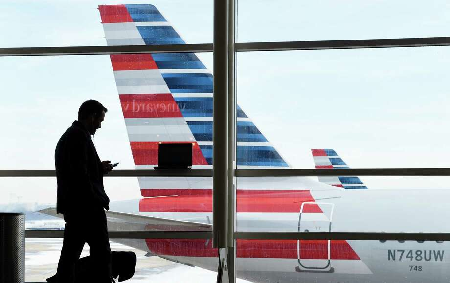 FILE - In this Jan. 25, 2016, file photo, a passenger talks on the phone as American Airlines jets sit parked at their gates at Washington's Ronald Reagan National Airport.  (AP Photo/Susan Walsh, File) Photo: Susan Walsh, STF / AP