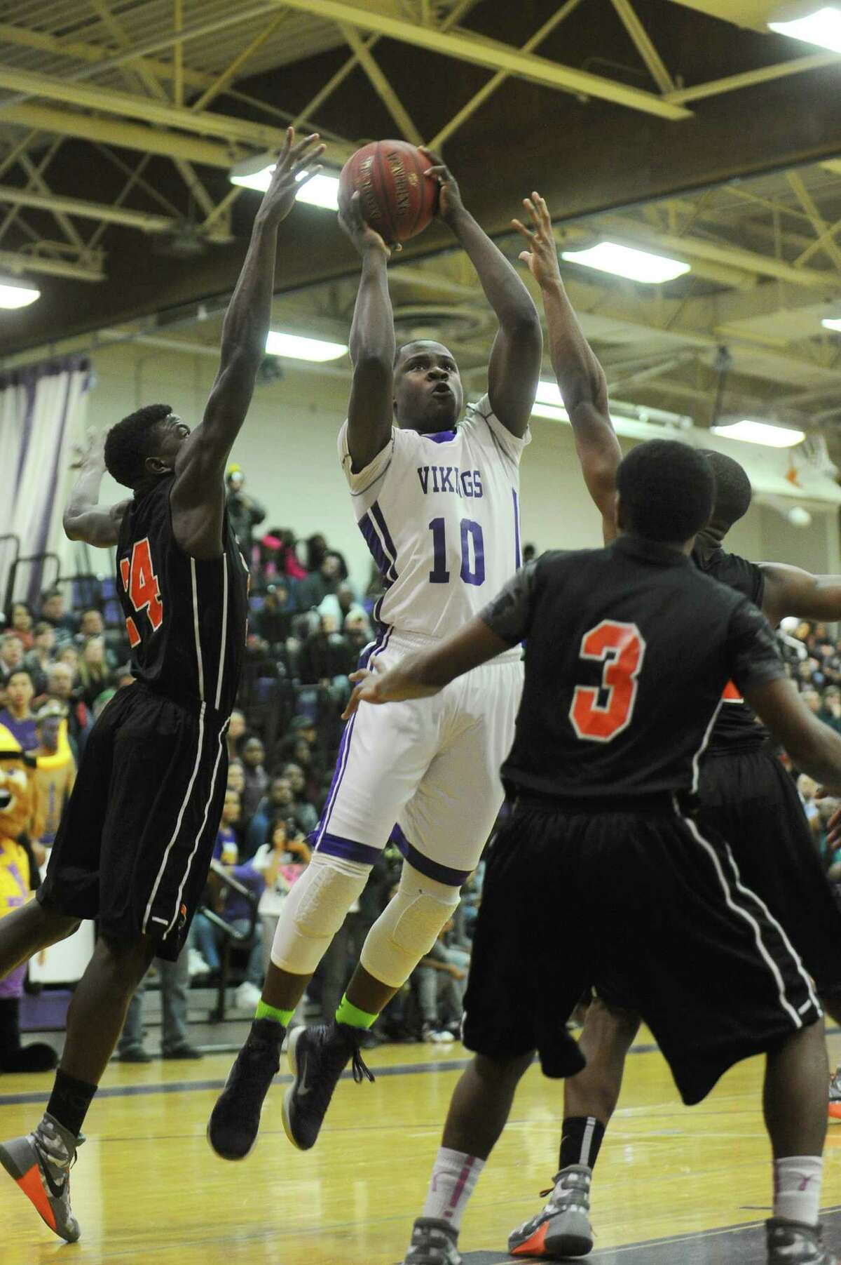 Westhill senior Tyrell Alexander gets a shot off between three Stamford High defenders during the first quarter of the game at Westhill High School on Monday, Feb. 1, 2016.
