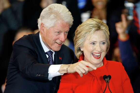 Former President Bill Clinton, left, and Democratic presidential candidate Hillary Clinton acknowledge supporters during a caucus night rally at Drake University in Des Moines, Iowa, Monday, Feb. 1, 2016.