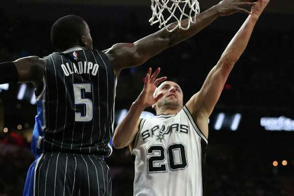 San Antonio Spurs' Manu Ginobili shoots around Orlando Magic's Victor Oladipo during the first half at the AT&T Center, Monday, Feb. 1, 2016