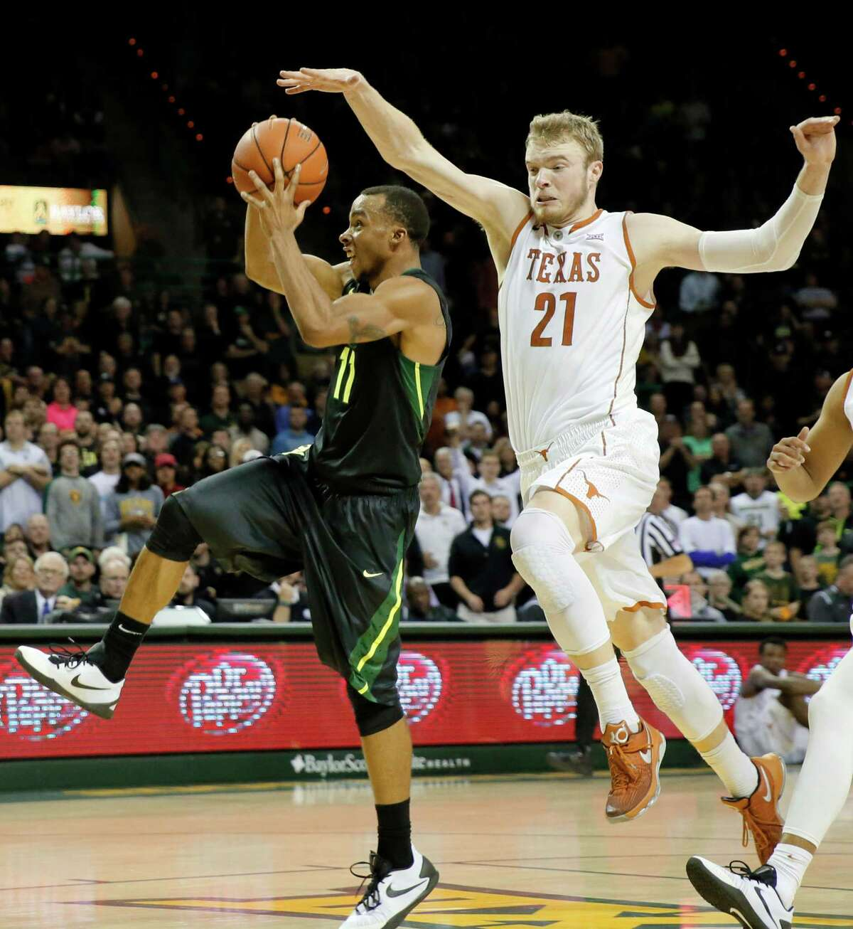 Baylor guard Lester Medford (11) goes up for a shot attempt as Texas forward Connor Lammert (21) defends in the second half of an NCAA college basketball game, Monday, Feb. 1, 2016, in Waco, Texas. Texas won 67-59. (AP Photo/Tony Gutierrez)