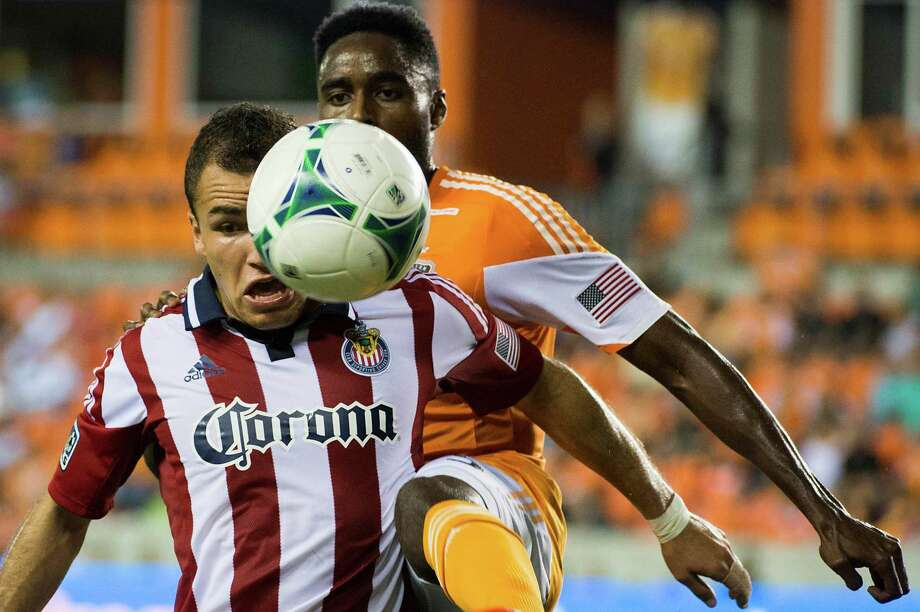 Chivas USA midfielder Carlos Alvarez (front) fights for the ball against Houston Dynamo defender Warren Creavalle during the first half in MLS action on Sept. 21, 2013, at BBVA Compass Stadium in Houston. Photo: Houston Chronicle / © 2013  Houston Chronicle