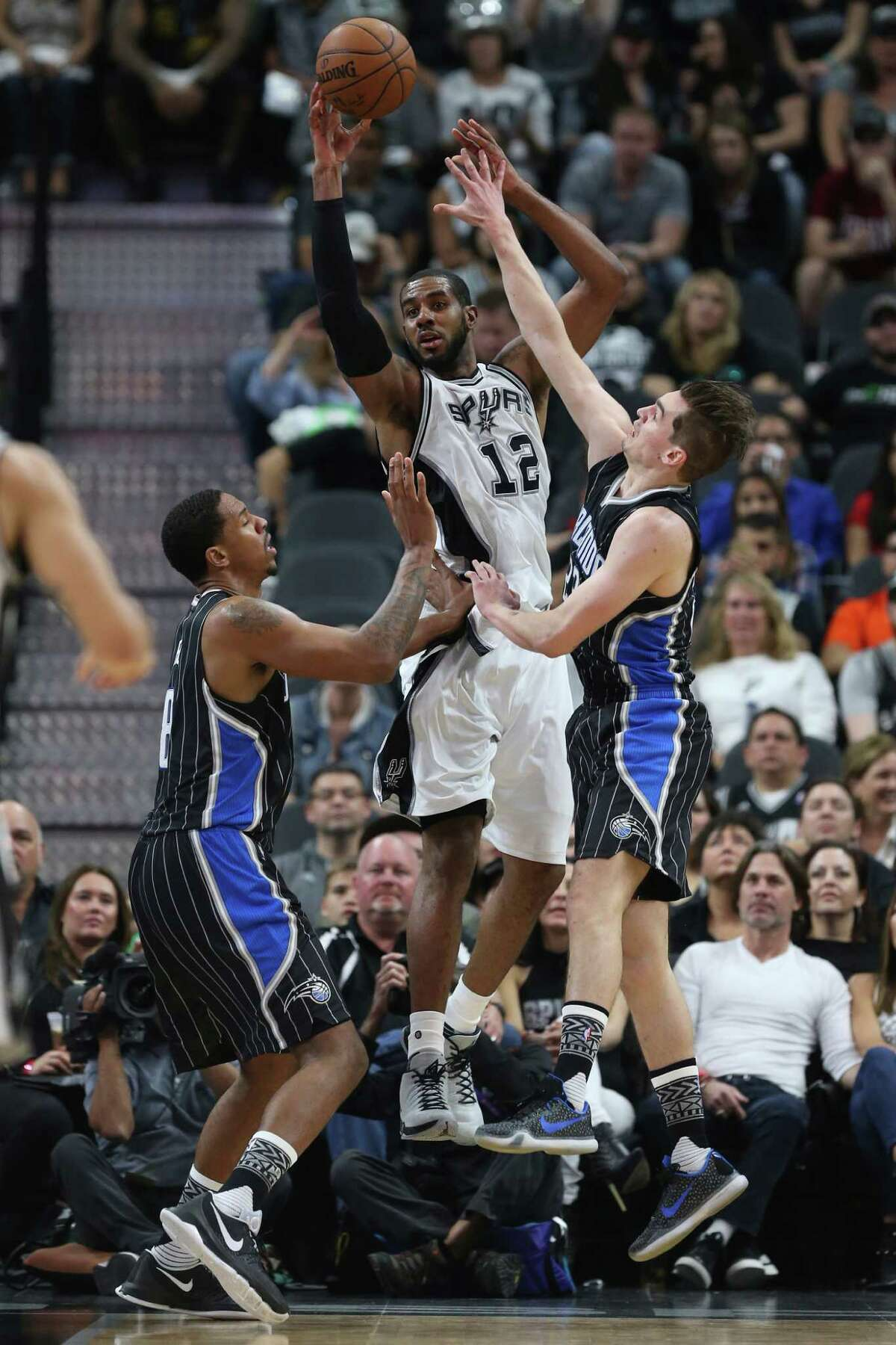 San Antonio Spurs' LaMarcus Aldridge passes between Orlando Magic's Channing Frye, left, and Mario Hezonja during the second half at the AT&T Center, Monday, Feb. 1, 2016