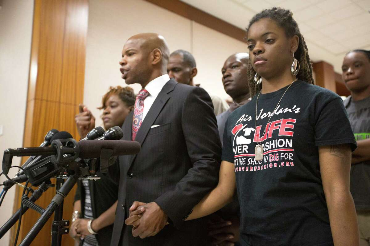 Joshlyn Walls, right, listens as Community activist Deric Muhammad speaks at a press conference regarding the death of Joshua Woods at the Harris County Criminal Courthouse, Tuesday, Feb. 2, 2016, in Houston. Woods, the brother to Walls, was a young man allegedly killed for his Air Jordan shoes in 2012. The trial for the accused was set to begin at 11 a.m.