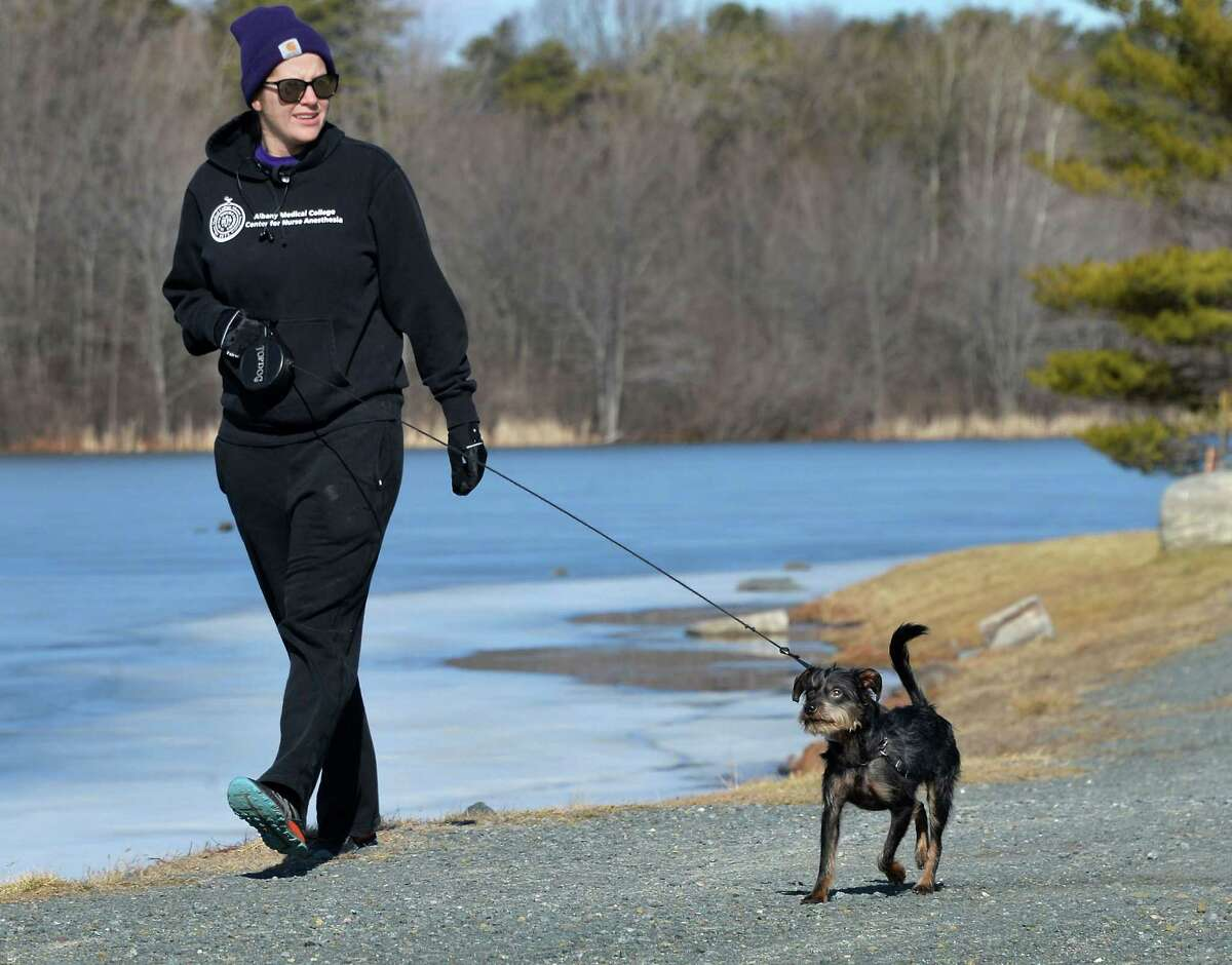 Sarah Collins of Cropseyville and her dog Rusty take a sunny walk around Rensselaer Lake Tuesday Feb. 2, 2016 in Albany, NY. (John Carl D'Annibale / Times Union)
