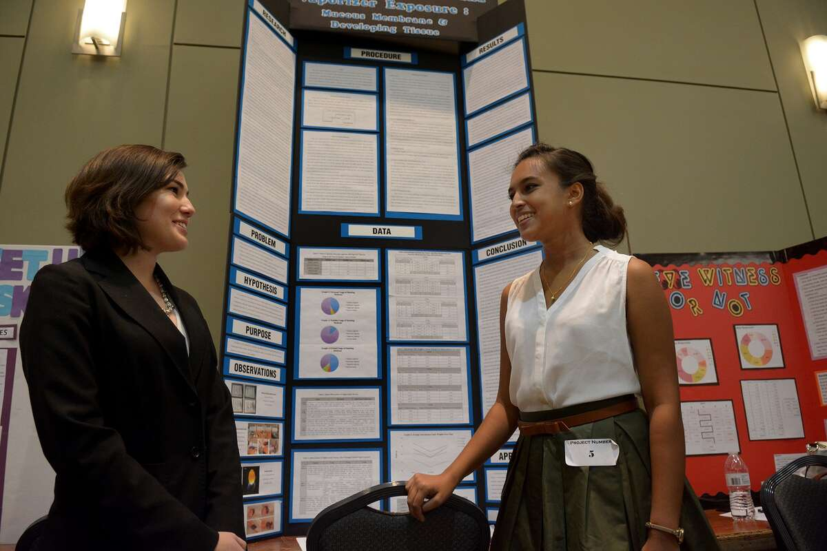 Juliana Steward, 16, left, and Megan Alam, 16, both juniors at the Academy of Science & Technology at College Park High School, shows off their project, titled E-Cigarette and Vaporizer Exposure: Mucuos Membrane & Developing Tissue, at the CISD district- wide science fair at the Lone Star Convention Center in Conroe on Jan. 29, 2016. (Photo by Jerry Baker/Freelance)