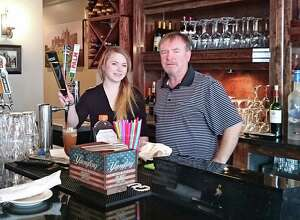 Manager Dana Verdon and co-owner Kevin O'Halloran behind the bar at The Castle on Post restaurant tat recently opened on the Post Road.