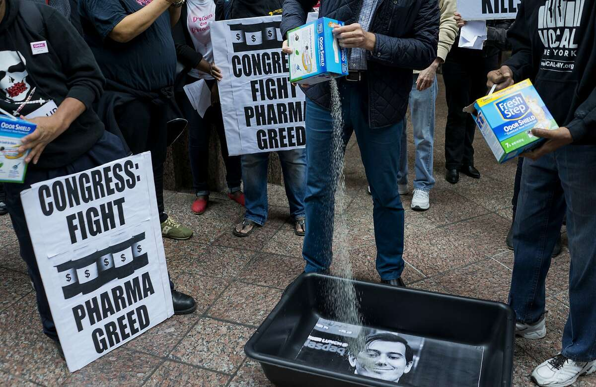FILE - In this Oct. 1, 2015 file photo, AIDS activists pour cat litter on an image of Turing Pharmaceuticals CEO Martin Shkreli in a makeshift cat litter pan during a protest highlighting pharmaceuticaldrug pricing in New York. Shkreli, the former hedge fund manager under fire for buying a pharmaceutical company and ratcheting up the price of a life-saving drug, is in custody following a securities probe, Thursday, Dec. 17, 2015. (AP Photo/Craig Ruttle)