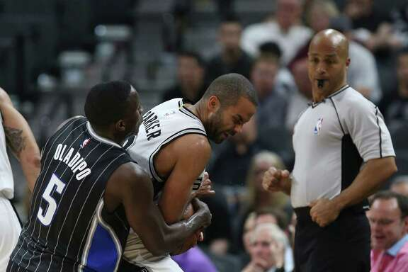 Spurs' Tony Parker gets tied up by Orlando Magic's Victor Oladipo as official Marc Davis watches during the second half at the AT&T Center on Feb. 1, 2016.