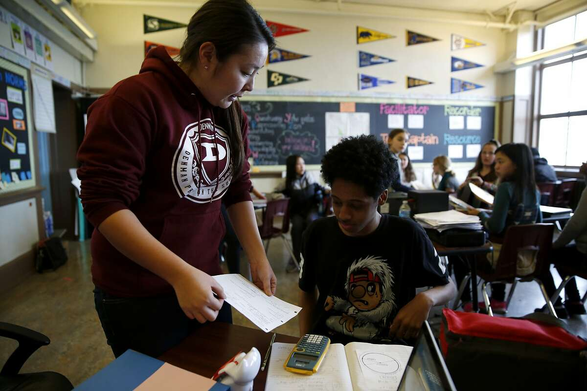 Teacher Yuka Walton helps a student with his math homework in advisory class at James Denman Middle School in San Francisco, California, on Tuesday, Feb. 2, 2016.