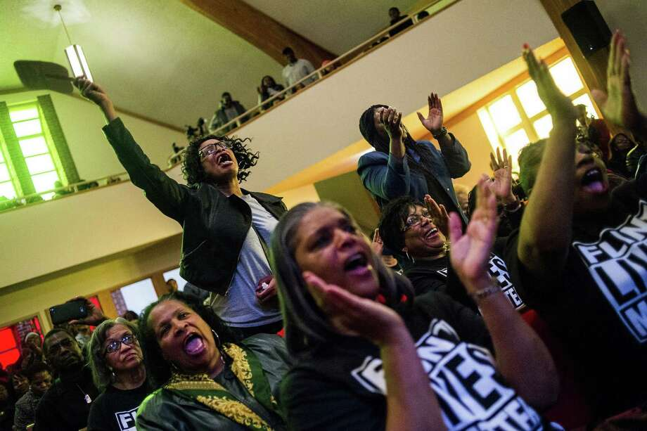 Flint resident Sharon Moore, left, leaps up to shout out her support as she listens to pastor David Bullock during a town hall meeting packed with more than 500 people to discuss the ongoing Flint water crisis on Monday, Feb. 1, 2016 at First Trinity Missionary Baptist Church in Flint, Mich. Flint switched its water source from Detroit's water system to the Flint River in 2014 to save money while under state financial management. The river water was not treated properly and lead from pipes leached into Flint homes. (Jake May/The Flint Journal - MLive.com via AP) Photo: Jake May, MBI / The Flint Journal