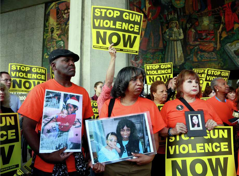 Parents of victims of gun violence, pastor Ruett Foster, from left, his wife Rhonda and Anna Del Rio hold pictures of their late children, during a rally supporting a city ordinance to ban the possession of high-capacity gun magazines outside Los Angeles City Hall, Tuesday, July 28, 2015. The Los Angeles City Council has voted to ban possession of high-capacity gun magazines in the wake of several deadly mass shootings around the country. (AP Photo/Nick Ut) Photo: Nick Ut, STF / AP