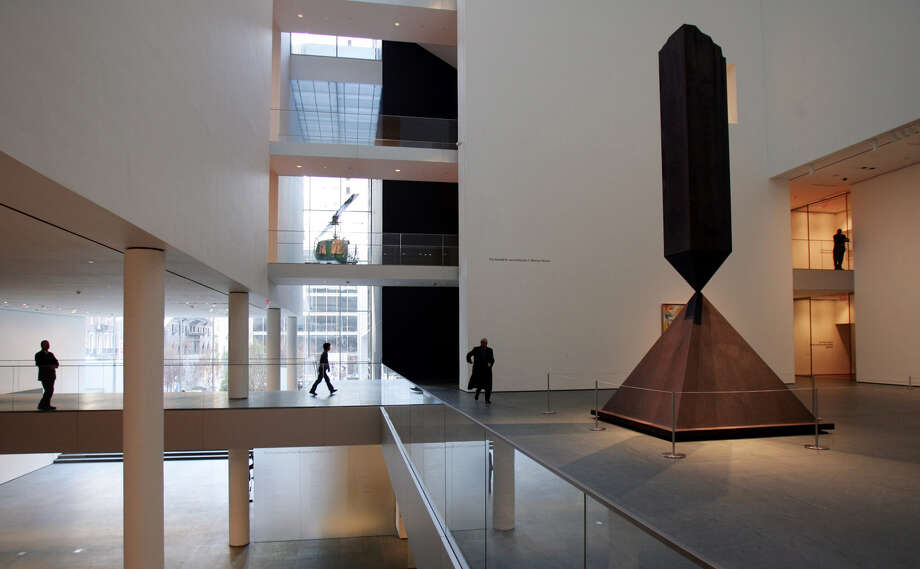 Barnett Newman's Broken Obelisk rises in MoMA's luminous atrium toward the skylight six stories above. The design by Japanese architect Yoshio Taniguchi expanded the sculpture garden and created light-filled, ample galleries that accommodate such large works as this self portrait by Chuck Close. (Photo from 2004.) Photo: ZACK SECKLER, AP / AP