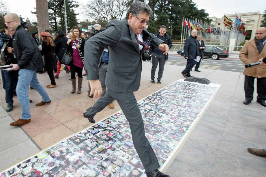 Syria's High Negotiations Committee, HNC, spokesman Salem al-Mislet jumps over pictures of the Syrian victims of the war displayed in front of the European headquarters of the United Nations, in Geneva, Switzerland, Tuesday, Feb. 2, 2016, where Syria peace talks continue. (Salvatore Di Nolfi/Keystone via AP) Photo: Salvatore Di Nolfi, SUB / KEYSTONE