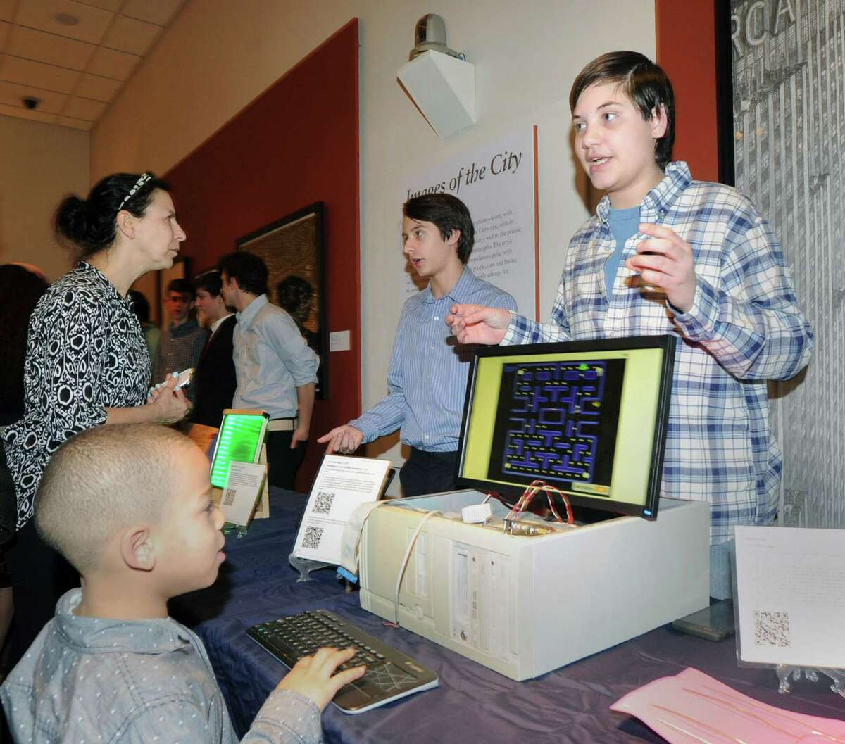 """Greenwich High School sophomore James Bonney, 16, right, explains his computer game """"Modernism Pacman"""" to a group of people during the exhibition of the Humanities and Modernism projects created by the Greenwich High School sophomores who are members of the Innovation Lab program at the Bruce Museum in Greenwich, Conn., Tuesday night, Feb. 2, 2016. Innovation Lab member Bonney said he made the game from his father's old computer and logic board. At left, seated, playing the game is Julian Curtiss School student Collin Batts, 6. According to Julie Faryniarz, executive director of the Greenwich Alliance for Education, research and development for the GHS Innovation Lab was funded through a grant provided by the Greenwich Alliance Reaching Out Grants program."""