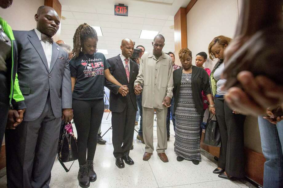 Activist Deric Muhammad, third from left, leads supporters of Joshua Woods in prayer Tuesday at the Harris County Criminal Courthouse. Photo: Cody Duty, Staff / © 2015 Houston Chronicle