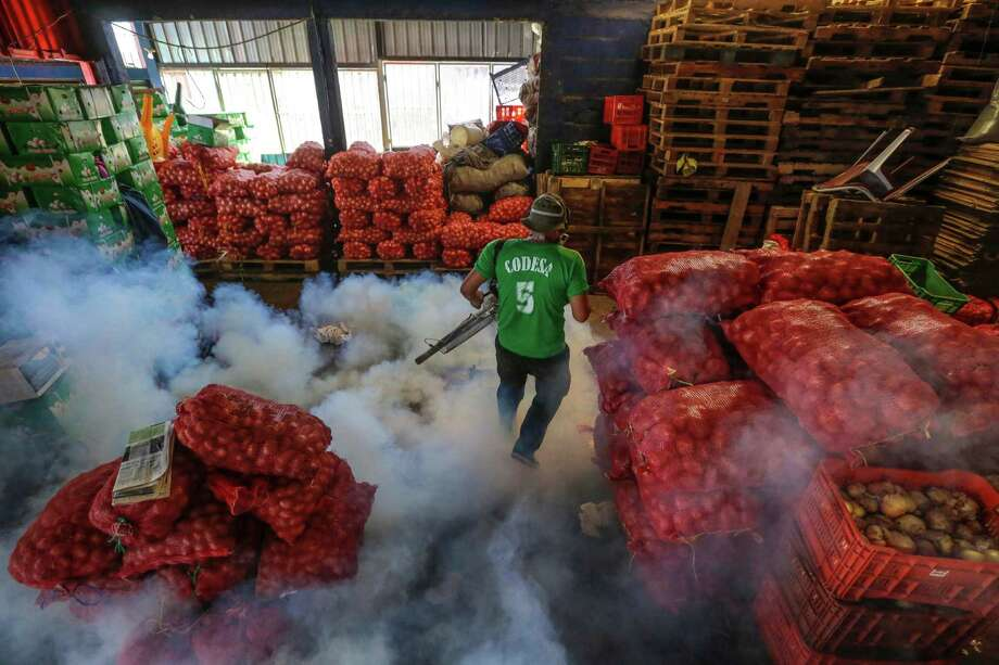 A Health Ministry worker fumigates for the Aedes aegypti mosquitoes that transmits the Zika virus at the Oriental Market in Nicaragua. Photo: Inti Ocon, STR / AP