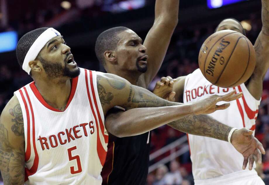 The Rockets' Josh Smith, left, and the Heat's Chris Bosh become entangled during Tuesday night's game at Toyota Center. Smith, who started at center for the short-handed Rockets, scored 19 points. Photo: Pat Sullivan, STF / AP