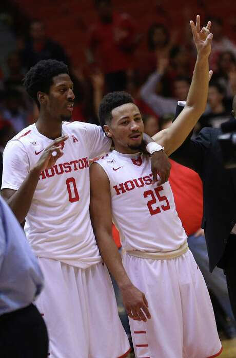 """Danrad """"Chicken"""" Knowles, left, who stuck around during UH's lean times, and Galen Robinson Jr., one of the young players contributing this season, savor UH's victory Monday night. Photo: Elizabeth Conley, Staff / © 2016 Houston Chronicle"""