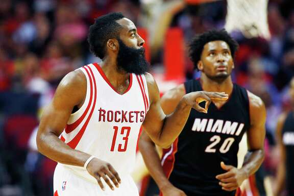 HOUSTON, TX - FEBRUARY 02:  James Harden #13 of the Houston Rockets reacts to a basket as Justise Winslow #20 of the Miami Heat looks on during their game at the Toyota Center on February 2, 2016  in Houston, Texas. NOTE TO USER: User expressly acknowledges and agrees that, by downloading and or using this Photograph, user is consenting to the terms and conditions of the Getty Images License Agreement.