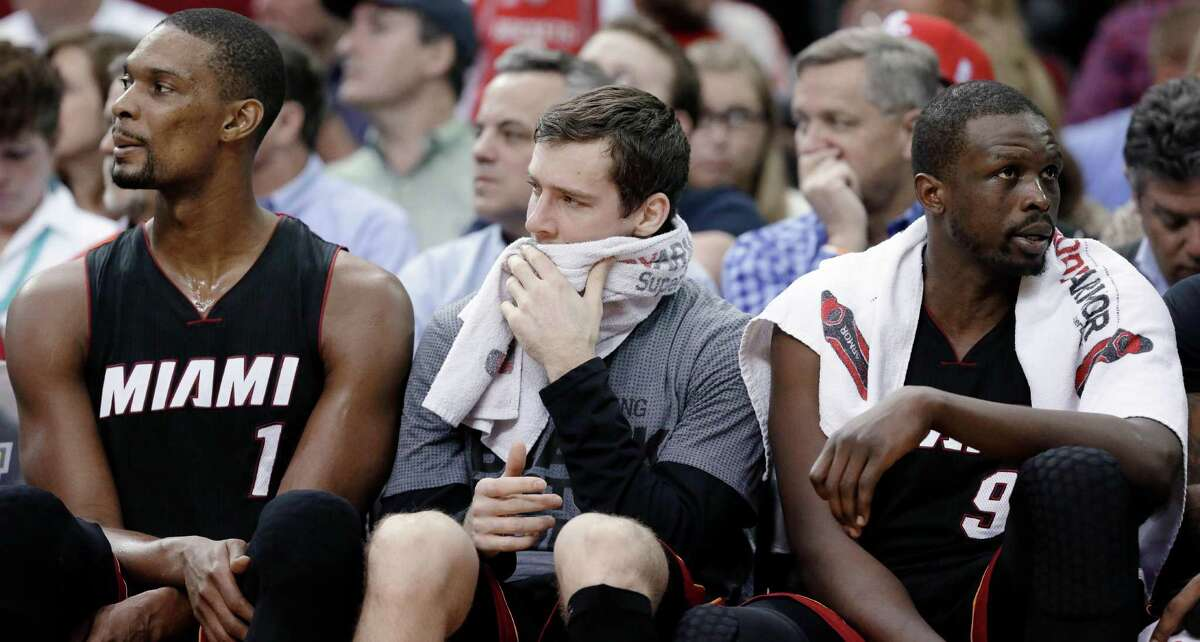 Miami Heat's Chris Bosh (1), Goran Dragic and Luol Deng (9) sit on the bench in the final minutes of an NBA basketball game against the Houston Rockets pn Tuesday, Feb. 2, 2016, in Houston. The Rockets won 115-102. (AP Photo/Pat Sullivan)