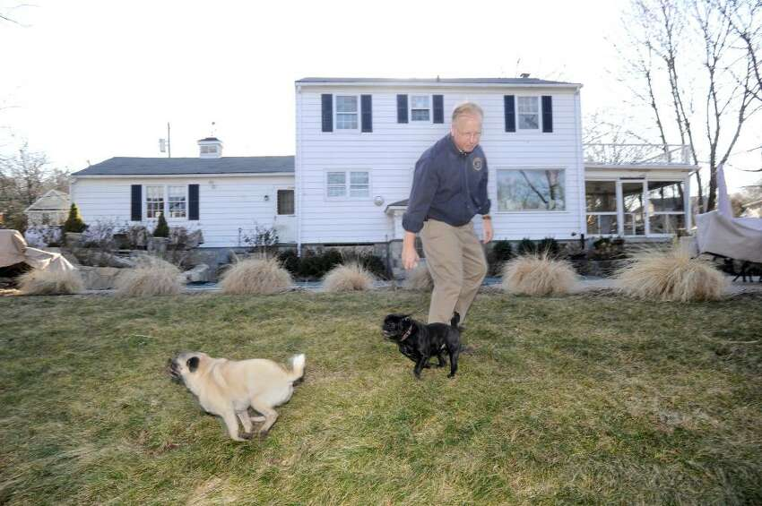 Mayor Mark Boughton in the back yard of his Alan Road home in Danbury with his pugs, Buddy and Spike on Monday, March 8, 2010. Boughton is a Republican candidate for governor.
