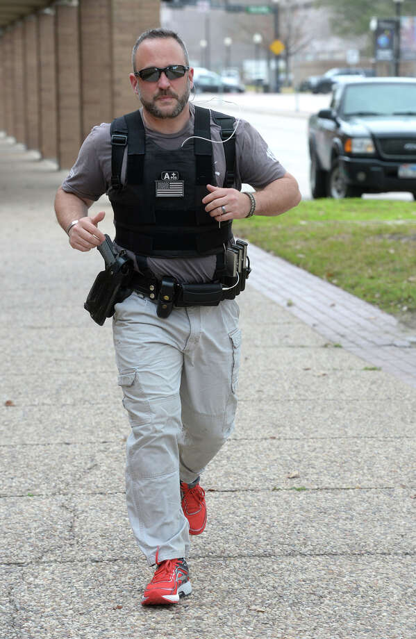 Aaron Lewallen runs while wearing his police gear in downtown Beaumont Tuesday to train for the upcoming Gusher Marathon. Lewallen said he is running the race to raise money for the Officer Bryan Hebert Memorial Scholarship. Hebert was killed in the line of duty in 2011. Photo taken Tuesday Guiseppe Barranco/The Enterprise Photo: Guiseppe Barranco, Photo Editor