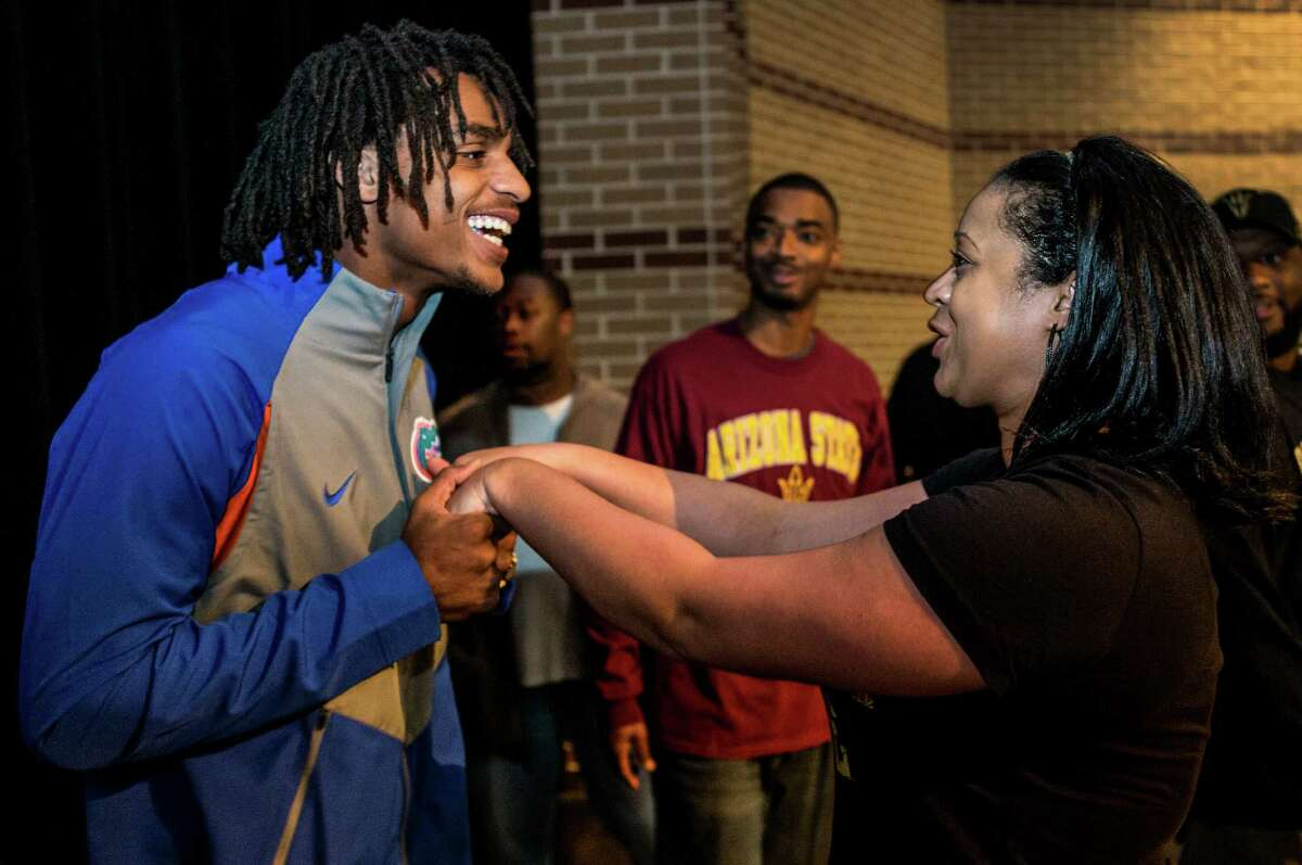 Tyrie Cleveland, left, is congratulated by Shalynndrea Sterling-Cole, mother of teammate Dillon Sterling-Cole, after he signed a letter of intent to play football at Florida during National Signing Day ceremonies at Westfield High School on Wednesday, Feb. 3, 2016, in Houston.