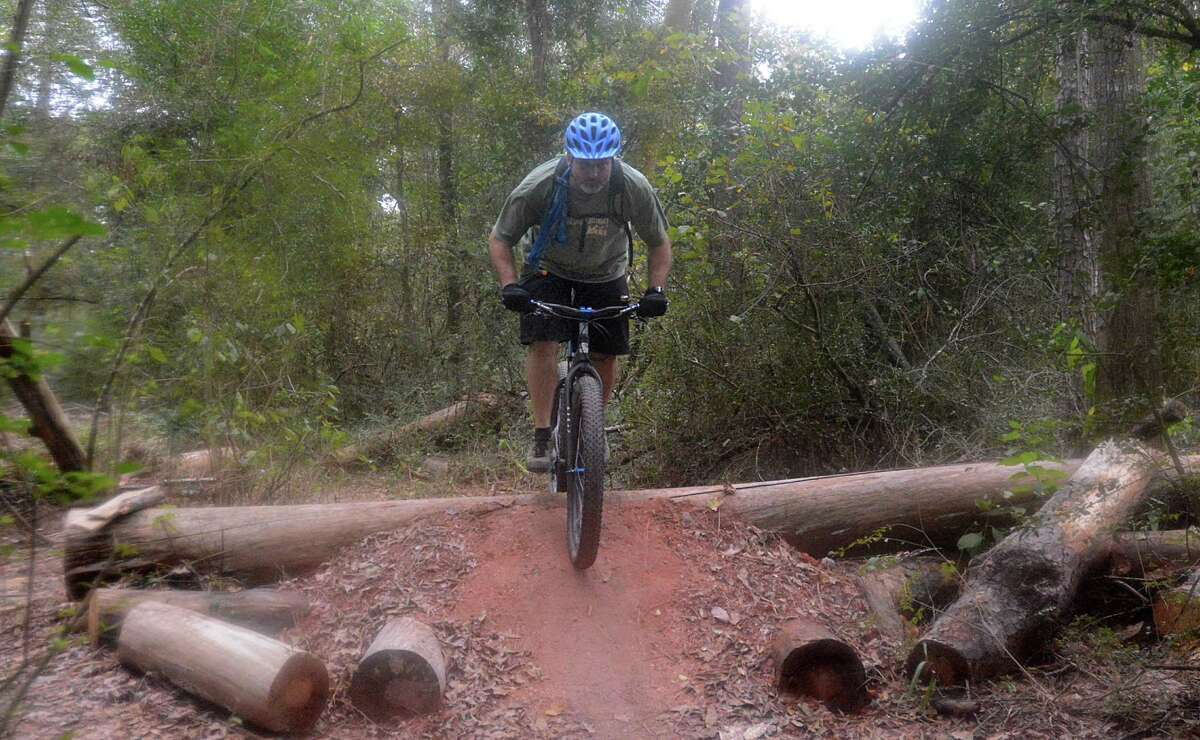 Scott Moran of Cypress jumps an obstacle on the bike trails at the 100 Acre Wood Preserve.