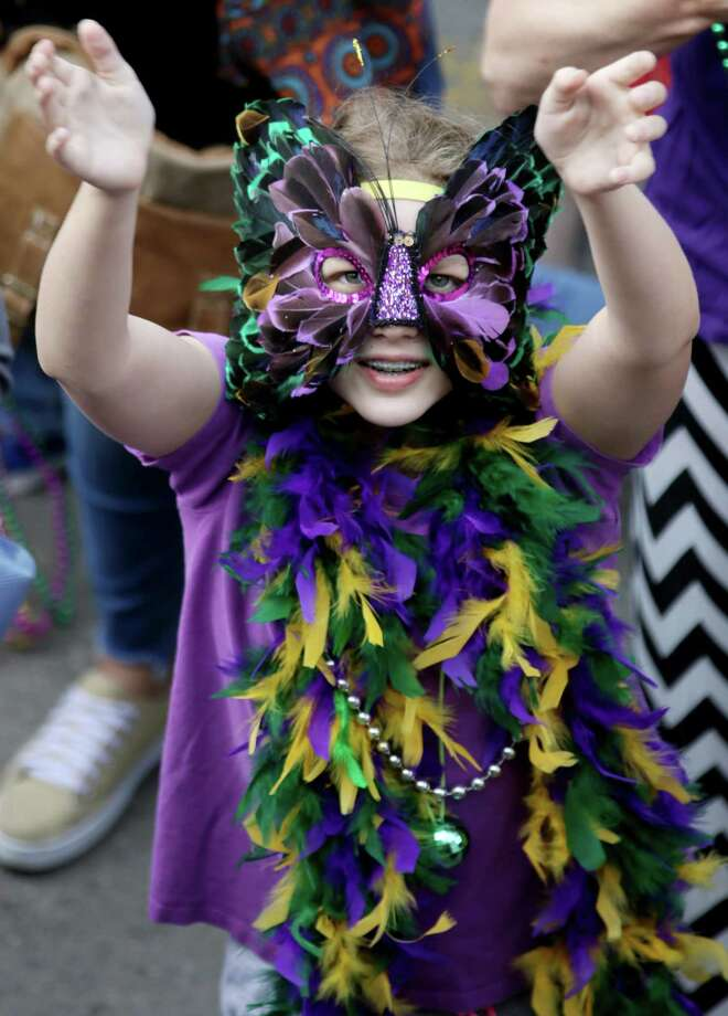Emma McCrory, 12, reaches to the sky for beads before the Sunshine Kids Parade along the Strand in Galveston. Photo: Jon Shapley, Staff / © 2015  Houston Chronicle