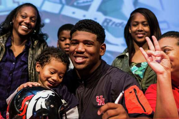 Ed Oliver, sits with his little brother, Justin Baker, and mother, Dana Baker, before Oliver signed a letter of intent to play football at Houston, during National Signing Day ceremonies at Westfield High School on Wednesday, Feb. 3, 2016, in Houston.