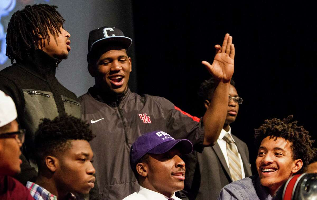 University of Houston signee Ed Oliver dons a Citadel cap he borrowed from Citadel signee Joshua Leblanc, lower right, as he and his teammates pose for photos during National Signing Day ceremonies at Westfield High School on Wednesday, Feb. 3, 2016, in Houston.