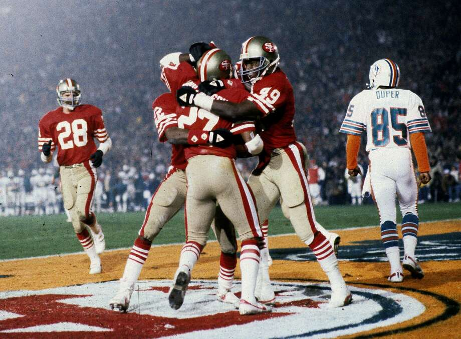 Teammats mob San Francisco 49ers safety Carlton Williamson (27) after Williamson intercepts a pass during Super Bowl XIX, a 38-16 victory over the Miami Dolphins on January 20, 1985, at Stanford Stadium in Stanford, California. (Photo by Rob Brown/Getty Images) *** Local Caption *** Photo: Rob Brown, NFL